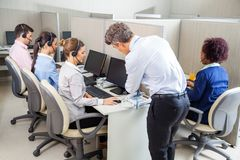Manager Assisting Customer Service Agent In Call. Manager assisting young female customer service agent while employees working in call center Royalty Free Stock Images