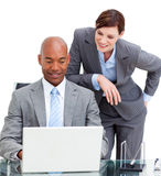 A manager assisting her colleague at a computer Stock Photos