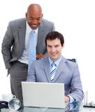Manager assisting his colleague at a computer Royalty Free Stock Images
