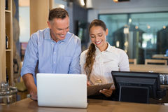 Manager and bartender discussing over clipboard in bar. Smiling manager and bartender discussing over clipboard in bar Stock Photos