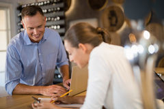 Manager and bartender discussing over clipboard in bar. Smiling manager and bartender discussing over clipboard in bar Royalty Free Stock Photography