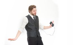 Manager with beard on inspired face. Businessman or ceo listen music. Man in formal outfit with mobile phone. Headset and mp3. Fashion and new technology Royalty Free Stock Photography