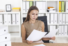 Manager in beige reading documents Stock Images