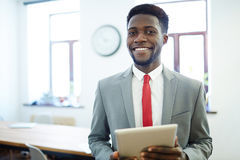 Manager in business attire. Successful employer with tablet looking at camera Stock Photos