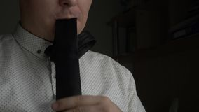 Manager or businessman eating his tie at dark office. Manager or businessman in white shirt eating his tie at dark office stock footage