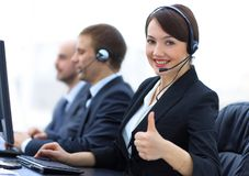 Manager of the call centre shows thumb up sitting at your Desk. In the workplace Stock Photos