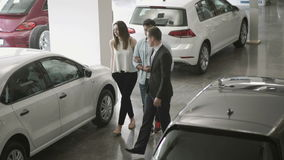 The manager of car showroom demonstrates the automobiles to young couple. Young couple chooses the automobile in car showroom. Smart manager in suit demonstrates stock footage