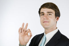 Manager cesticulate contentment. Head-and-shoulder view of a young man to dark suit against white background showing the OK sign and friendly smiling into the Stock Images