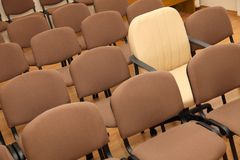 Manager chair among ordinary chairs. Manager chair stands out among the rows of ordinary office chairs Royalty Free Stock Photos