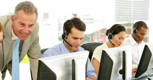 Manager checking on call centre employees stock footage