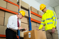 Manager Checking List With Worker In Warehouse Stock Photos