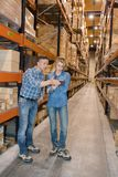 Manager checking tablet with worker in warehouse Stock Photos