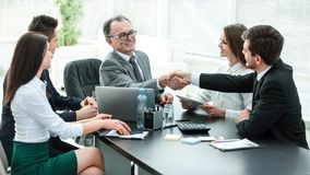 Manager and client shaking hands after discussing the contract stock photography