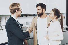 Manager and client with wife are shaking hands in kitchen store. Stock Image
