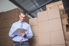 Manager with clipboard in warehouse. Portrait of manager holding clipboard against boxes in the warehouse Royalty Free Stock Photos