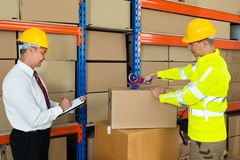 Manager With Clipboard And Worker Taping Box Stock Photography