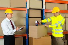 Manager With Clipboard And Worker Taping Box Royalty Free Stock Photo