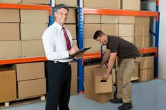 Manager With Clipboard And Worker In Warehouse Royalty Free Stock Image