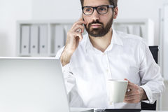 Manager with coffee on the phone Royalty Free Stock Photos