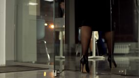 The Manager comes out of the office with glass doors. Slow motion, evening time stock video