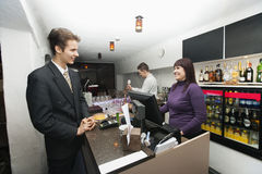 Manager communicating with cashier at bar counter Stock Photos