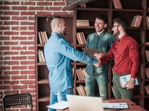 Manager of the company welcomes the customer with a handshake in Royalty Free Stock Photos