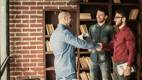 Manager of the company welcomes the customer with a handshake in. Handshake when meeting the Manager and the client in the office.the photo has a empty space for Stock Photo