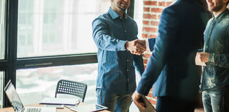 Manager of the company welcomes the customer with a handshake in Stock Image