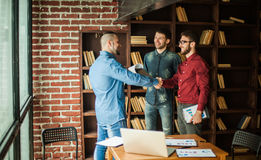 Manager of the company welcomes the customer with a handshake in Stock Photography