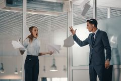 Manager conflicts with subordinate. Angry boss fights aggressively with a subordinate or colleague in a suit. Throws all the paper documents on the floor and royalty free stock photo