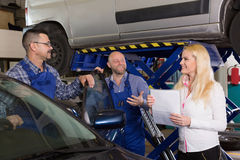 Manager and crew doing check up of broken car Royalty Free Stock Photo