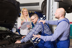 Manager and crew doing check up of broken car Stock Photo