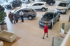 Manager, customer and cars in showroom of dealership Nissan in Nizhny Novgorodcity in 2018 royalty free stock photo