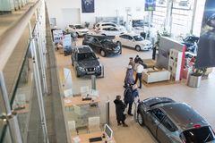 Manager, customer and cars in showroom of dealership Nissan in Nizhny Novgorodcity in 2018 stock photography