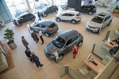 Manager, customer and cars in showroom of dealership Nissan in Nizhny Novgorodcity in 2018 stock photo