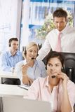 Manager at customer service. Manager checking customer service operators in office Royalty Free Stock Photography
