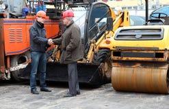Manager der Arbeiten in den harten Hüten, die Hände rütteln Stockbild