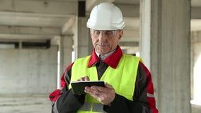 Manager der Arbeiten mit elektronischem Gerät an der Baustelle stock footage