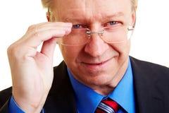 Manager, der über seinen Gläsern schaut Lizenzfreie Stockfotografie