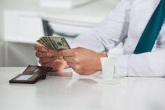 Manager, der Dollarscheine zählt Stockfotografie