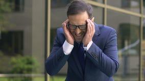 Manager, der extrem starke Migräne, leidende Kopfschmerzen von den Stadtgeräuschen hat stock video footage