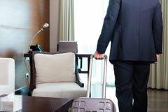 Manager in der Klage, die in Hotelzimmer mit seinem Koffer sich bewegt Lizenzfreies Stockfoto