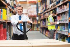Manager, der Laufkatze mit Kästen vor seinem Angestellten zieht Lizenzfreies Stockfoto