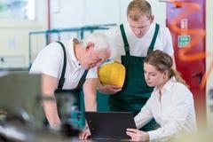 Manager, der mit Betriebsarbeitskräften spricht Stockbilder