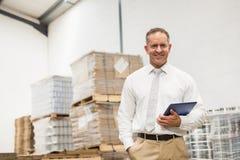 Manager, der mit der Hand in der Tasche hält Tabletten-PC steht Stockfoto