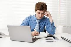 Manager, der am Schreibtisch im Büro sitzt Stockbild
