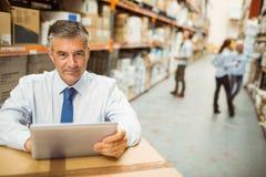 Manager, der an Tabletten-PC beim Betrachten der Kamera arbeitet Lizenzfreies Stockfoto