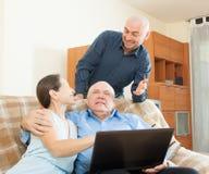 Manager, der zu den älteren Paaren mit Laptop hilft Stockbild