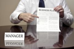Manager At Desk Holding Business Plan Document Stock Image
