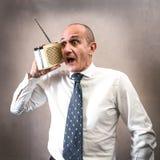 Manager die aan de radio luisteren die vreemde uitdrukkingen maken royalty-vrije stock foto's